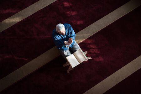 Photo pour Young Arabic Muslim man reading Koran and praying. Religious muslim man reading holy koran inside the mosque. - image libre de droit