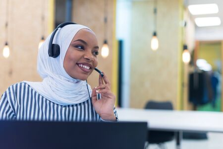 Photo pour African muslim female with hijab scarf customer representative business woman with phone headset helping and supporting online with customer in modern bright call centre. - image libre de droit