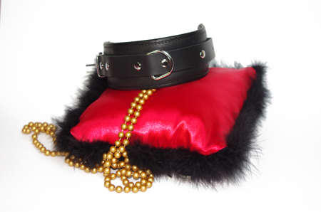 An isolated shot of a quality leather collar on red pillow with beads