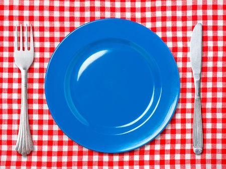 Empty blue dinner plate with fork and knife on red and white checked tablecloth.