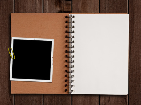 Photo pour White paper notebook with photograph on wooden table. - image libre de droit