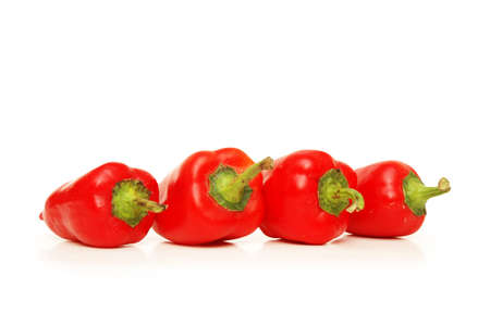 Four red chili peppers isolated on white