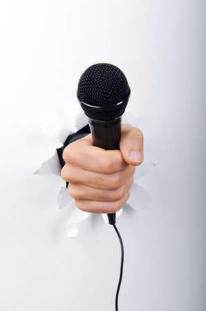 Hand holding microphone through hole in paper