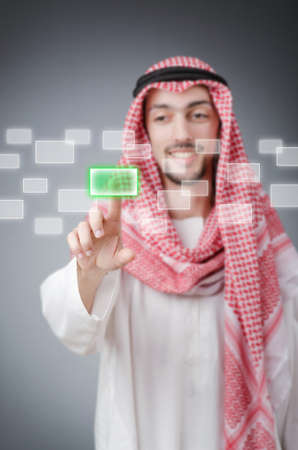 Young arab pressing virtual buttonsの写真素材