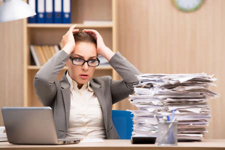 Foto de Businesswoman under stress from too much work in the office - Imagen libre de derechos