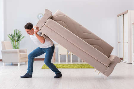 Photo pour Man moving furniture at home - image libre de droit