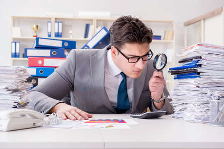 Photo pour Male businessman with magnifying glass in office - image libre de droit