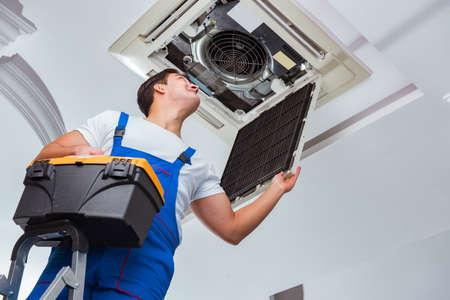 Photo for Worker repairing ceiling air conditioning unit - Royalty Free Image