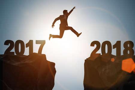 Photo pour Businessman looking forward to 2018 from 2017 - image libre de droit