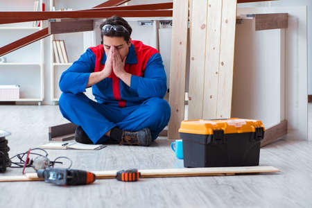 Photo pour Young carpenter at work tired feeling not well - image libre de droit