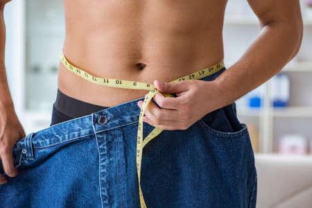 Photo pour Man in oversized pants in weight loss concept - image libre de droit