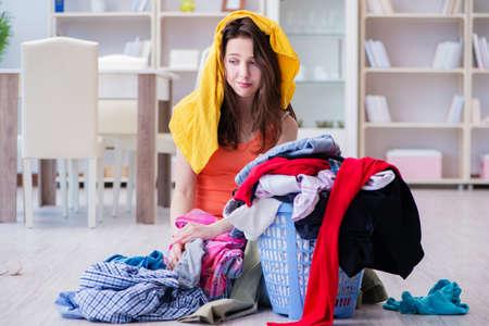 Photo pour Stressed woman doing laundry at home - image libre de droit