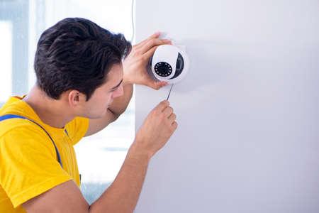 Photo pour Contractor installing surveillance CCTV cameras in office - image libre de droit