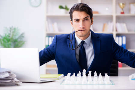 Photo pour Young businessman playing glass chess in office - image libre de droit