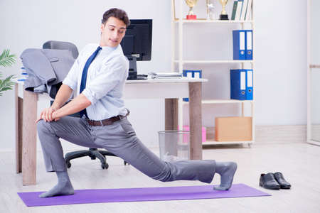 Foto de Businessman doing sports in office during break - Imagen libre de derechos