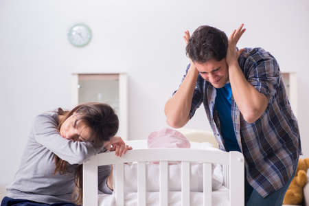 Photo pour Young dad cannot stand baby crying - image libre de droit