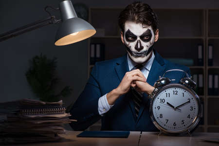 Foto de Businessman with scary face mask working late in office - Imagen libre de derechos
