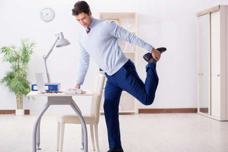 Photo for Employee doing stretching exercises in the office - Royalty Free Image