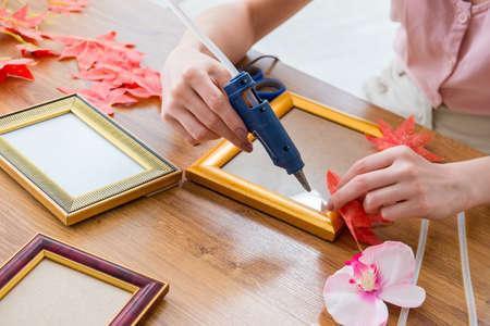 Photo pour Woman decorating picture frame in scrapbooking concept - image libre de droit
