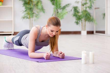 Foto de Young woman exercising in sports hall in healthy concept - Imagen libre de derechos