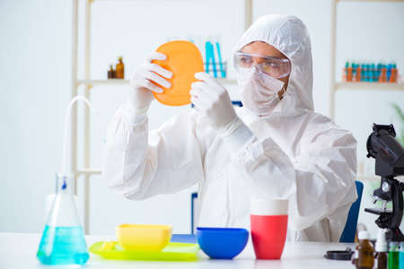 Photo for Chemist checking and testing plastic dishes - Royalty Free Image