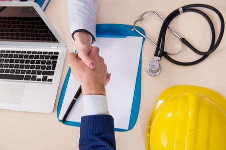 Photo pour Doctor and manager agreeing industrial insurance coverage - image libre de droit