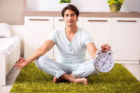 Foto de Young man doing yoga in bedroom in time management concept - Imagen libre de derechos