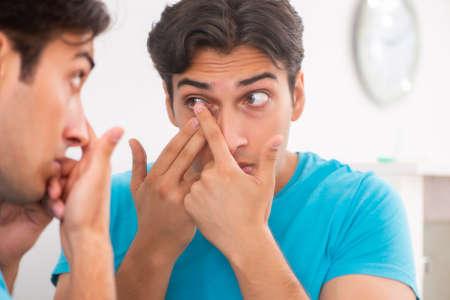 Photo pour Man trying contact lenses at home - image libre de droit