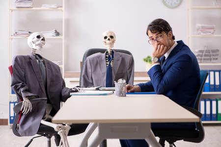 Foto de Funny business meeting with boss and skeletons - Imagen libre de derechos