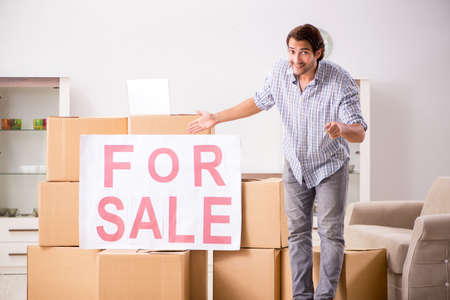 Photo pour Young man offering home for sale and moving out - image libre de droit