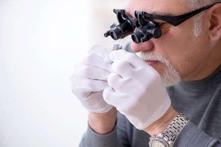 Photo pour White bearded old jeweler at workshop - image libre de droit
