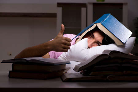 Photo pour Male handsome student preparing for exams late at home - image libre de droit