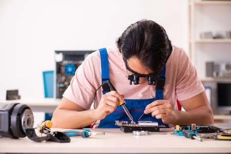 Photo pour Young male contractor repairing computer - image libre de droit