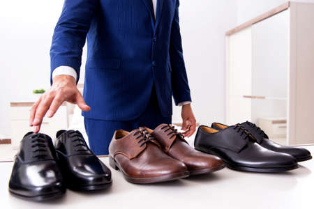 Foto de Young handsome businessman choosing shoes at home - Imagen libre de derechos