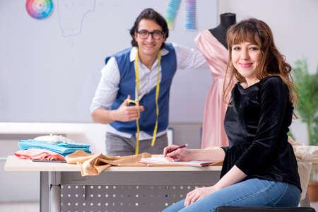 Photo pour Young male tailor teaching female student - image libre de droit