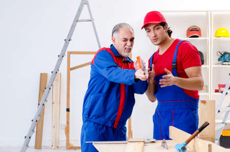 Photo for Two professional contractors laying flooring at home - Royalty Free Image