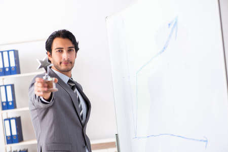 Photo pour Young handsome businessman in front of whiteboard - image libre de droit