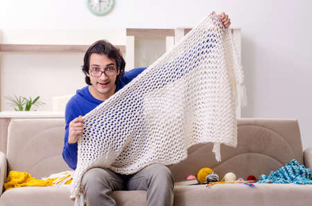 Photo for Young good looking man knitting at home - Royalty Free Image