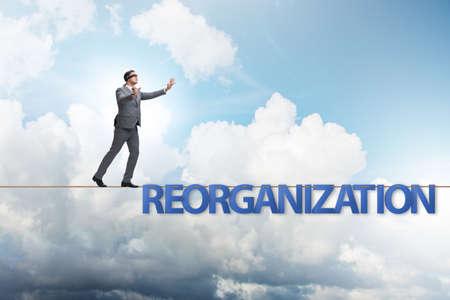 Photo pour Reorganisation concept with businessman walking on tight rope - image libre de droit