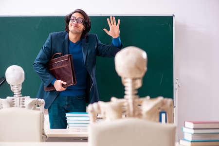 Photo pour Male teacher and skeleton student in the classroom - image libre de droit