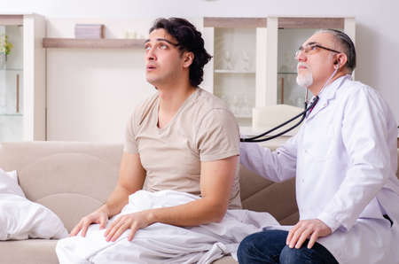 Photo for Old male doctor visiting young male patient - Royalty Free Image