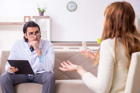 Photo pour Young female patient discussing with male psychologist personal - image libre de droit