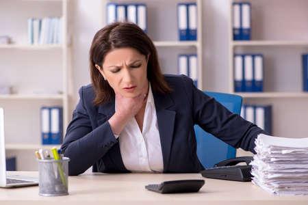Foto de Middle-aged female employee suffering in the office - Imagen libre de derechos