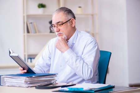 Foto de Old male doctor working in the clinic - Imagen libre de derechos