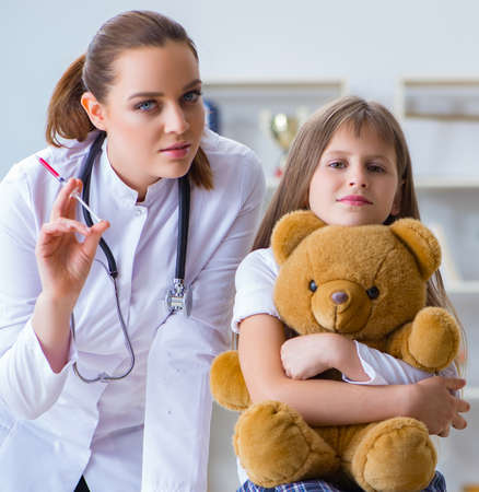 Photo pour Woman female doctor examining little cute girl with toy bear - image libre de droit