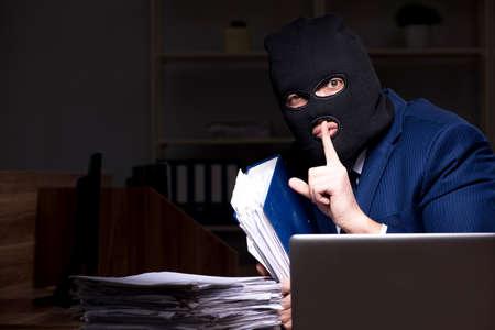 Foto de Male employee stealing information in the office night time - Imagen libre de derechos