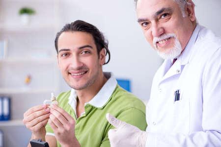 Photo pour Male patient with hearing problem visiting doctor otorhinolaryng - image libre de droit