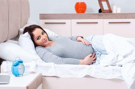 Photo pour Young pregnant woman in the bedroom - image libre de droit