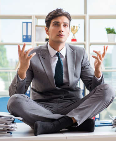Photo for Businessman sitting on top of desk in office - Royalty Free Image