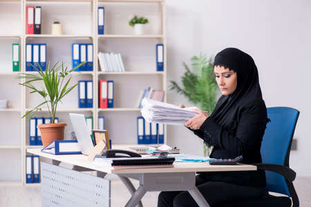 Photo pour Female employee bookkeeper in hijab working in the office - image libre de droit